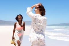 Deux amis de jeunes femmes jouant sur la plage Images libres de droits