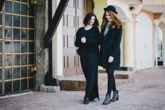Deux amis de jeunes femmes marchant sur une rue Photos stock