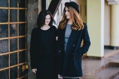 Deux amis de jeunes femmes marchant sur une rue Images stock