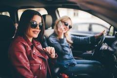 Deux amis de jeunes femmes parlant ensemble dans la voiture d'o pendant qu'ils partent en voyage par la route tandis que le condu Images stock