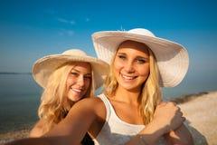 Deux amis de jeunes femmes prenant le selfie sur la plage Photos libres de droits