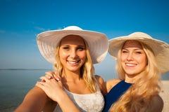Deux amis de jeunes femmes prenant le selfie sur la plage Image stock