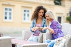Deux amis de l'adolescence de femme ayant l'amusement en café extérieur Photographie stock libre de droits
