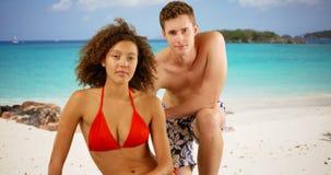 Deux amis de métis se reposant sur la plage dans les Caraïbe Photographie stock