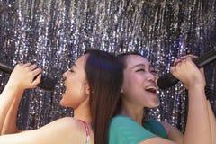 Deux amis de nouveau au dos tenant des microphones et chantant ensemble au karaoke Photos stock