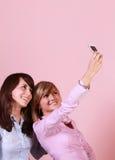 Deux amis de sourire à l'aide du téléphone portable pour une photo Images libres de droits