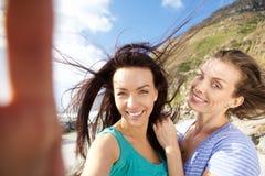 Deux amis de sourire appréciant prenant des selfies Image libre de droits