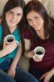 Deux amis de sourire ayant le café et regardant l'appareil-photo sur le c Photo stock