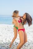 Deux amis de sourire dans des bikinis jouant ensemble Photographie stock libre de droits