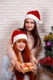 Deux amis de sourire dans Santa couvre se reposer près de l'arbre de Noël Photos stock