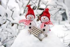 Deux amis de sourire de bonhommes de neige dans la neige Photographie stock libre de droits