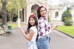 Deux amis de sourire de femme à l'aide du téléphone intelligent Photos libres de droits