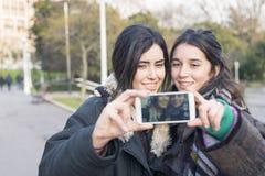 Deux amis de sourire de femme faisant le selfie Image libre de droits