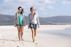 Deux amis de sourire de femmes marchant sur la plage ensemble Image libre de droits