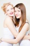Deux amis de sourire heureux de femmes embrassant et souriant dans le studio Image stock