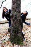 Deux amis de sourire jetant un coup d'oeil par derrière un arbre Photo stock