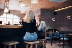 Deux amis de sourire lisant la causerie en ligne drôle au téléphone moderne se reposant avec du café savoureux dans le restaurant Image libre de droits