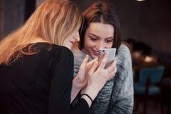 Deux amis de sourire lisant la causerie en ligne drôle au téléphone moderne se reposant avec du café savoureux dans le restaurant Photographie stock libre de droits