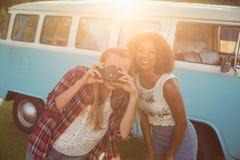 Deux amis de sourire photographiant avec l'appareil-photo Image stock