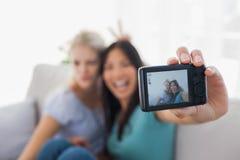 Deux amis de sourire prenant la photo avec l'appareil-photo Photographie stock