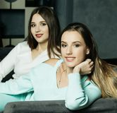 Deux amis de sourire s'asseyant sur le divan regardant l'appareil-photo dans le salon à la maison Photo stock