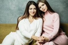 Deux amis de sourire s'asseyant sur le divan regardant l'appareil-photo dans le salon à la maison Photo libre de droits