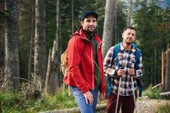 Deux amis de sourire trimardant dans la région sauvage Images stock