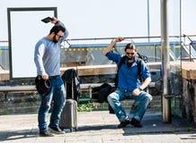 Deux amis deviennent fous en raison du retard d'autobus Images stock