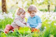 Deux amis drôles d'enfants dans des oreilles de lapin de Pâques pendant l'oeuf chassent Photographie stock libre de droits