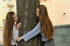 Deux amis dupent autour, regardant par derrière un arbre Image libre de droits