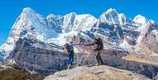 Deux amis en montagnes s'aidant Image libre de droits