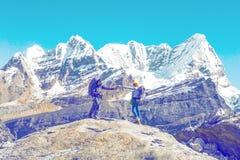 Deux amis en montagnes s'aidant léger Images stock