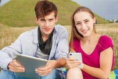 Deux amis en parc avec le PC de téléphone portable et de comprimé Image stock