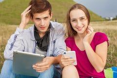 Deux amis en parc avec le PC de téléphone portable et de comprimé Photo stock