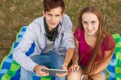 Deux amis en parc avec le PC de téléphone portable et de comprimé Photographie stock libre de droits