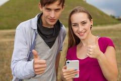 Deux amis en parc avec le téléphone portable Émotions positives Photographie stock