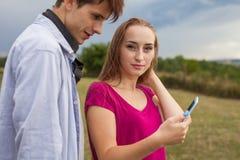 Deux amis en parc avec le téléphone portable Jeunes adultes Photos stock