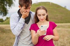 Deux amis en parc avec le téléphone portable Jeunes adultes Images stock