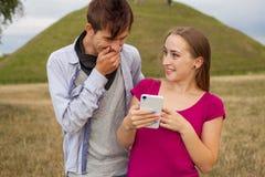 Deux amis en parc avec le téléphone portable Jeunes adultes Photo stock