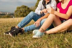 Deux amis en parc avec le téléphone portable Jeunes adultes Photo libre de droits