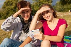 Deux amis en parc avec le téléphone portable Jeunes adultes Images libres de droits