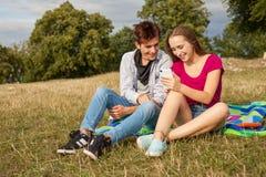 Deux amis en parc avec le téléphone portable Jeunes adultes Photos libres de droits