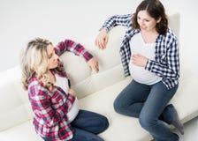 Deux amis enceintes ayant une causerie se reposant sur le sofa Photos libres de droits