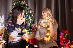 Deux amis féminins à côté d'un arbre de Noël décoré Photographie stock libre de droits