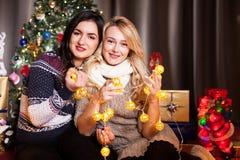 Deux amis féminins à côté d'un arbre de Noël décoré Image libre de droits