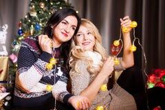 Deux amis féminins à côté d'un arbre de Noël décoré Photographie stock