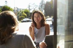 Deux amis féminins à l'aide d'un ordinateur portable parlant en dehors d'un café Photo stock