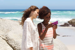 Deux amis féminins à la plage regardant le téléphone portable Photographie stock