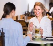 Deux amis féminins à la table de café Photographie stock