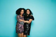 Deux amis féminins étreignant au-dessus du fond bleu Photos libres de droits